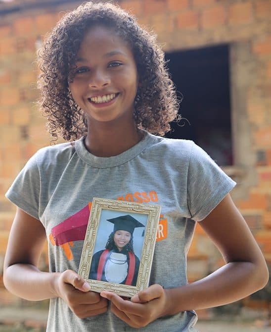 Sponsored Child in Brazil Holding Her Graduation Picture